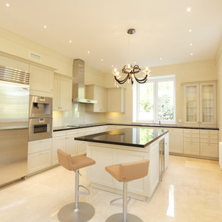 Mid-sized transitional l-shaped separate kitchen in Moscow with a double-bowl sink, louvered cabinets, beige cabinets, quartzite benchtops, beige splashback, porcelain splashback, stainless steel appliances, porcelain floors, with island, beige floor and black benchtop.