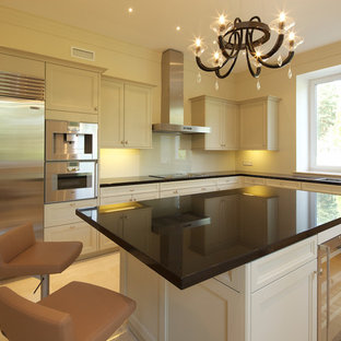Design ideas for a mid-sized transitional l-shaped separate kitchen in Moscow with a double-bowl sink, louvered cabinets, beige cabinets, quartzite benchtops, beige splashback, porcelain splashback, stainless steel appliances, porcelain floors, with island, beige floor and black benchtop.