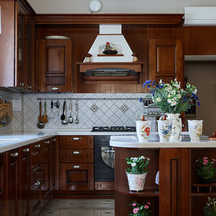 Свежая идея для дизайна: кухня в классическом стиле с врезной раковиной, фасадами цвета дерева среднего тона, белым фартуком, черной техникой и островом - отличное фото интерьера