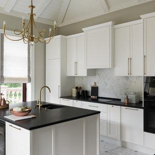 Удачное сочетание для дизайна помещения: параллельная кухня в стиле современная классика с белыми фасадами, белым фартуком, черной техникой, мраморным полом, островом, белым полом, фасадами в стиле шейкер и фартуком из мрамора - самое интересное для вас
