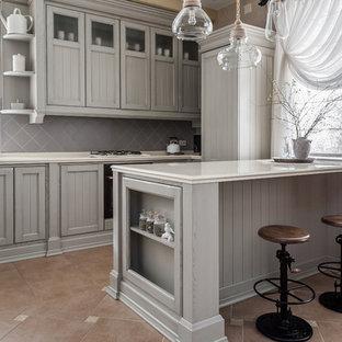 На фото: прямая кухня среднего размера в классическом стиле с обеденным столом, врезной раковиной, серыми фасадами, столешницей из акрилового камня, серым фартуком, фартуком из цементной плитки, черной техникой, полом из керамической плитки, островом, коричневым полом, бежевой столешницей и фасадами в стиле шейкер в частном доме с