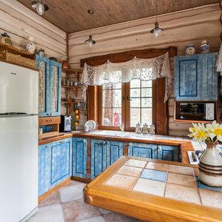 Ejemplo de cocina en U, rural, con fregadero encastrado, armarios con paneles con relieve, puertas de armario azules, península y encimera de azulejos
