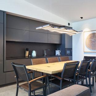 Неиссякаемый источник вдохновения для домашнего уюта: линейная кухня среднего размера в современном стиле с обеденным столом, монолитной раковиной, плоскими фасадами, черными фасадами, черным фартуком, черной техникой, полом из керамогранита, серым полом и черной столешницей без острова