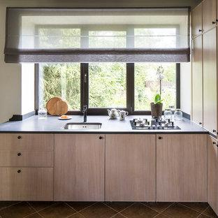 Неиссякаемый источник вдохновения для домашнего уюта: п-образная кухня-гостиная среднего размера в современном стиле с врезной раковиной, плоскими фасадами, светлыми деревянными фасадами, фартуком с окном, столешницей из гранита, техникой под мебельный фасад и полом из керамогранита
