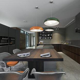 На фото: отдельная, угловая кухня в современном стиле с плоскими фасадами, темными деревянными фасадами, серым фартуком, техникой из нержавеющей стали и островом с