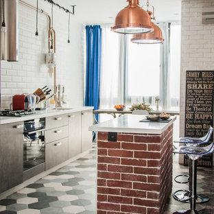 Идея дизайна: маленькая прямая кухня в стиле лофт с врезной раковиной, плоскими фасадами, серыми фасадами, столешницей из акрилового камня, белым фартуком, фартуком из плитки кабанчик, черной техникой, полом из керамогранита, островом, белой столешницей и разноцветным полом