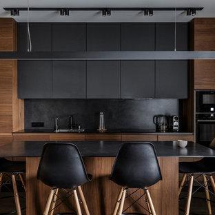 Свежая идея для дизайна: параллельная кухня среднего размера в современном стиле с обеденным столом, врезной раковиной, плоскими фасадами, темным паркетным полом, островом, темными деревянными фасадами, черным фартуком, фартуком из каменной плиты, черной техникой, коричневым полом и черной столешницей - отличное фото интерьера