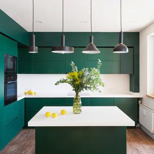 На фото: угловая кухня в современном стиле с врезной раковиной, плоскими фасадами, зелеными фасадами, белым фартуком, черной техникой, паркетным полом среднего тона, островом и белой столешницей с