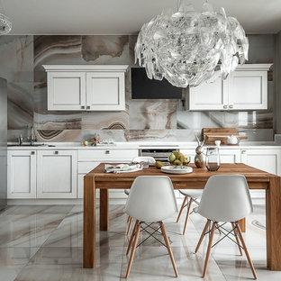 Пример оригинального дизайна: линейная кухня в современном стиле с накладной раковиной, фасадами с утопленной филенкой, белыми фасадами, разноцветным фартуком, техникой из нержавеющей стали, разноцветным полом и белой столешницей без острова