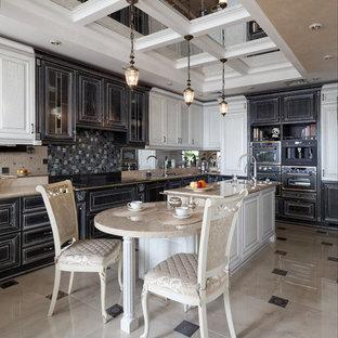 На фото: угловая кухня в классическом стиле с черными фасадами, черной техникой, островом и бежевым полом с