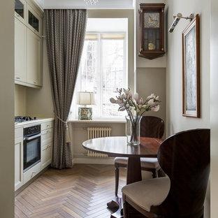 Idéer för ett avskilt klassiskt linjärt kök, med luckor med infälld panel, vita skåp, svarta vitvaror, mellanmörkt trägolv och brunt golv