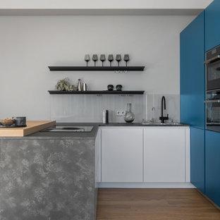 Неиссякаемый источник вдохновения для домашнего уюта: п-образная кухня среднего размера в современном стиле с двойной раковиной, плоскими фасадами, синими фасадами, фартуком из стекла, техникой под мебельный фасад, полуостровом, коричневым полом и серой столешницей