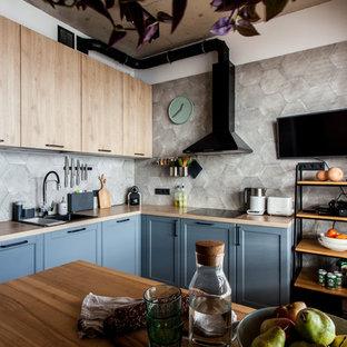 Пример оригинального дизайна: угловая кухня в современном стиле с обеденным столом, накладной раковиной, фасадами в стиле шейкер, синими фасадами, деревянной столешницей, серым фартуком, фартуком из цементной плитки, черной техникой и коричневой столешницей