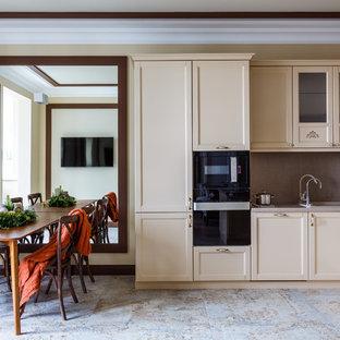 Идея дизайна: п-образная кухня-гостиная в стиле современная классика с накладной раковиной, фасадами в стиле шейкер, бежевыми фасадами, серым фартуком, черной техникой и полуостровом