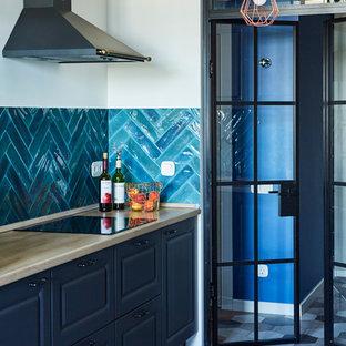 На фото: линейные кухни в современном стиле с фасадами с выступающей филенкой, черными фасадами, синим фартуком, серым полом, бежевой столешницей, деревянной столешницей, фартуком из керамической плитки и полом из цементной плитки без острова