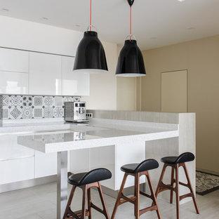 Foto de cocina escandinava, abierta, con armarios con paneles lisos, puertas de armario blancas, península, salpicadero verde y suelo gris