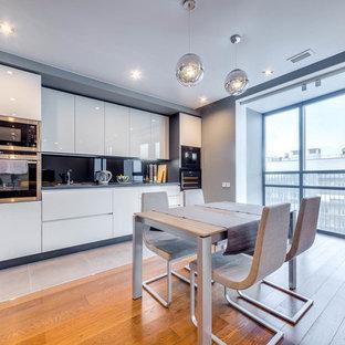 Идея дизайна: угловая кухня в современном стиле с обеденным столом, плоскими фасадами, белыми фасадами, черным фартуком, фартуком из стекла, техникой из нержавеющей стали, бежевым полом и серой столешницей