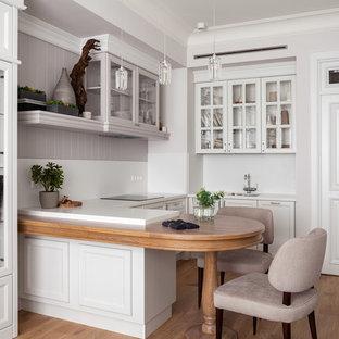 Стильный дизайн: п-образная кухня среднего размера в стиле современная классика с обеденным столом, врезной раковиной, белыми фасадами, столешницей из акрилового камня, белым фартуком, полуостровом, фасадами с утопленной филенкой и паркетным полом среднего тона - последний тренд