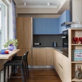 Ejemplo de cocina en L, actual, de tamaño medio, abierta, sin isla, con armarios con paneles lisos, suelo de madera en tonos medios, fregadero encastrado, salpicadero verde, suelo marrón, encimeras grises, puertas de armario azules y electrodomésticos con paneles