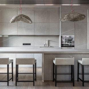 На фото: параллельная кухня-гостиная среднего размера в современном стиле с монолитной раковиной, плоскими фасадами, серыми фасадами, столешницей из известняка, серым фартуком, фартуком из известняка, техникой из нержавеющей стали, светлым паркетным полом, островом, бежевым полом и серой столешницей с
