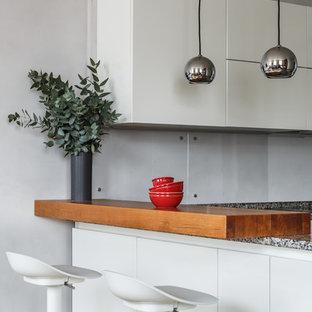 Неиссякаемый источник вдохновения для домашнего уюта: кухня-гостиная в современном стиле с плоскими фасадами, белыми фасадами, серым фартуком, фартуком из стекла и полуостровом