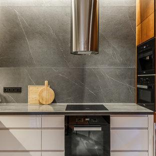 Свежая идея для дизайна: угловая кухня в современном стиле с обеденным столом, плоскими фасадами, белыми фасадами, столешницей из акрилового камня, серой столешницей, врезной раковиной, серым фартуком и черной техникой - отличное фото интерьера