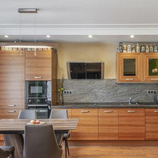 На фото: линейная кухня среднего размера в современном стиле с обеденным столом, накладной раковиной, плоскими фасадами, фасадами цвета дерева среднего тона, серым фартуком, черной техникой, паркетным полом среднего тона и серой столешницей без острова с