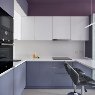 Modern inredning av ett mellanstort vit vitt u-kök, med en enkel diskho, släta luckor, lila skåp, vitt stänkskydd, svarta vitvaror, en halv köksö och grått golv
