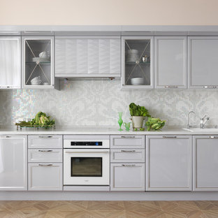 Пример оригинального дизайна: линейная кухня в стиле современная классика с накладной раковиной, фасадами с утопленной филенкой, серыми фасадами, фартуком из плитки мозаики, белой техникой, белой столешницей, разноцветным фартуком и светлым паркетным полом