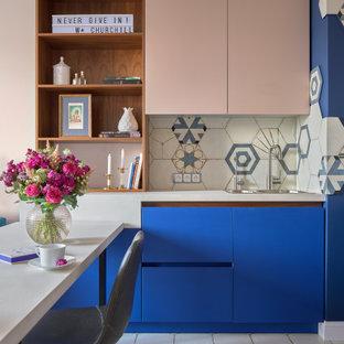 На фото: маленькая угловая кухня в современном стиле с обеденным столом, накладной раковиной, плоскими фасадами, синими фасадами, разноцветным фартуком, разноцветным полом и серой столешницей