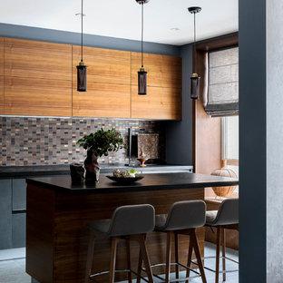 Modelo de cocina en L, contemporánea, de tamaño medio, abierta, con armarios con paneles lisos, puertas de armario grises, encimera de granito, salpicadero de azulejos de porcelana, suelo de baldosas de porcelana, una isla, suelo gris y encimeras negras