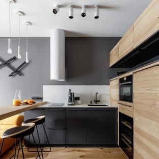 На фото: п-образная кухня-гостиная в современном стиле с врезной раковиной, плоскими фасадами, черными фасадами, белым фартуком, черной техникой, паркетным полом среднего тона, полуостровом, коричневым полом и белой столешницей