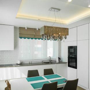 Стильный дизайн: угловая кухня-гостиная в современном стиле с врезной раковиной, плоскими фасадами, белыми фасадами, белым фартуком, фартуком из плитки кабанчик, черной техникой, серой столешницей, полом из винила и коричневым полом без острова - последний тренд