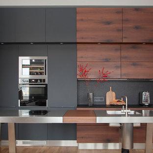 На фото: с высоким бюджетом линейные кухни среднего размера в современном стиле с обеденным столом, плоскими фасадами, черными фасадами, столешницей из гранита, черным фартуком, фартуком из каменной плиты, техникой из нержавеющей стали, паркетным полом среднего тона, островом, черной столешницей, монолитной раковиной и коричневым полом