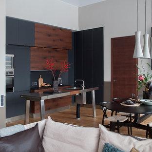 Inredning av ett modernt mellanstort svart svart kök, med en undermonterad diskho, släta luckor, svarta skåp, granitbänkskiva, svart stänkskydd, stänkskydd i sten, rostfria vitvaror, mellanmörkt trägolv, en köksö och gult golv