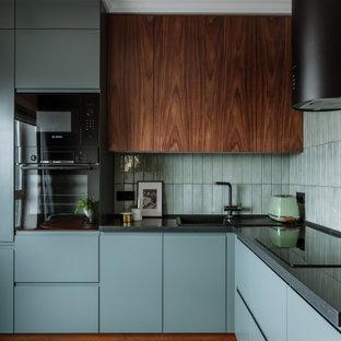 Пример оригинального дизайна: угловая кухня в современном стиле с накладной раковиной, плоскими фасадами, серыми фасадами, серым фартуком, черной техникой, серым полом и серой столешницей без острова