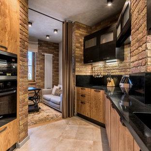他の地域のインダストリアルスタイルのおしゃれなL型キッチン (一体型シンク、フラットパネル扉のキャビネット、中間色木目調キャビネット、黒いキッチンパネル、黒い調理設備、ベージュの床、黒いキッチンカウンター) の写真