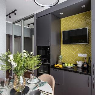 Свежая идея для дизайна: кухня в скандинавском стиле с плоскими фасадами, серыми фасадами, желтым фартуком, фартуком из плитки кабанчик, черной техникой, коричневым полом и черной столешницей - отличное фото интерьера