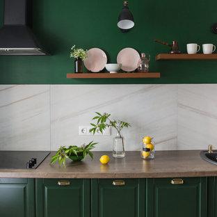 Пример оригинального дизайна: маленькая угловая кухня в классическом стиле с обеденным столом, накладной раковиной, фасадами с утопленной филенкой, зелеными фасадами, столешницей из ламината, бежевым фартуком, фартуком из керамогранитной плитки, черной техникой, полом из винила, коричневым полом и коричневой столешницей без острова
