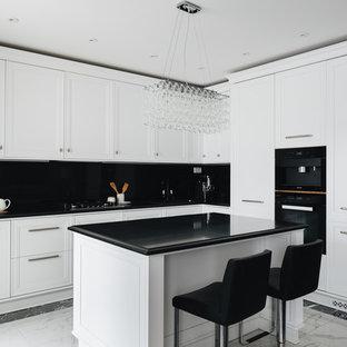 На фото: угловая кухня-гостиная в стиле современная классика с фасадами с утопленной филенкой, белыми фасадами, черным фартуком, черной техникой, островом, разноцветным полом и черной столешницей с