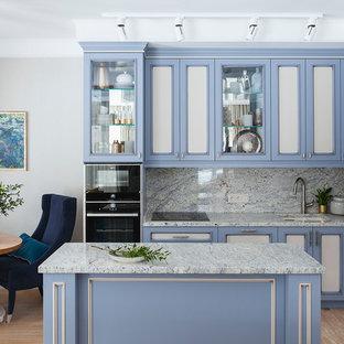 Пример оригинального дизайна: угловая кухня-гостиная в стиле неоклассика (современная классика) с врезной раковиной, фасадами с утопленной филенкой, синими фасадами, серым фартуком, черной техникой, островом, бежевым полом и серой столешницей