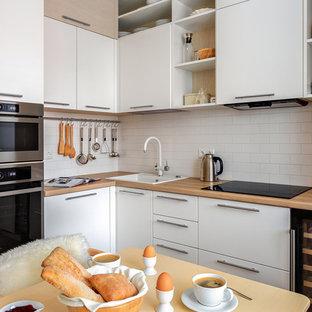 На фото: маленькая отдельная, угловая кухня в скандинавском стиле с накладной раковиной, плоскими фасадами, белыми фасадами, столешницей из ламината, белым фартуком, техникой из нержавеющей стали и фартуком из керамогранитной плитки без острова с