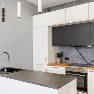 Стильный дизайн: параллельная кухня среднего размера в современном стиле с накладной раковиной, плоскими фасадами, белыми фасадами, деревянной столешницей, серым фартуком, техникой из нержавеющей стали, полуостровом и бежевой столешницей - последний тренд