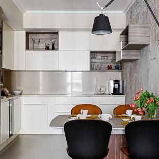 Свежая идея для дизайна: угловая кухня среднего размера в современном стиле с обеденным столом, плоскими фасадами, белыми фасадами, столешницей из акрилового камня, полом из керамической плитки, серым полом, серым фартуком и серой столешницей - отличное фото интерьера