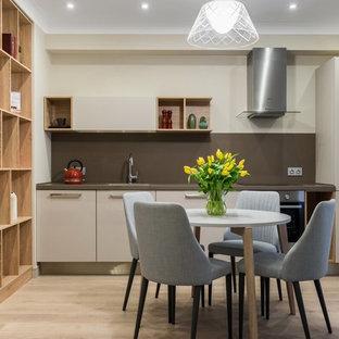 Стильный дизайн: линейная кухня-гостиная в современном стиле с плоскими фасадами, бежевыми фасадами, коричневым фартуком, техникой из нержавеющей стали, светлым паркетным полом и бежевым полом без острова - последний тренд