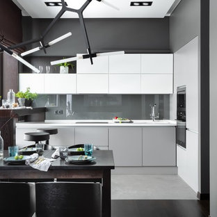 This is an example of a mid-sized contemporary l-shaped open plan kitchen in Moscow with an integrated sink, flat-panel cabinets, white cabinets, solid surface benchtops, grey splashback, black appliances, porcelain floors, no island, grey floor, white benchtop and glass sheet splashback.