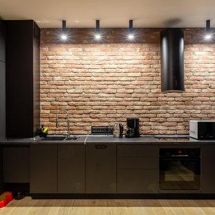 На фото: прямая кухня в стиле лофт с накладной раковиной, плоскими фасадами, черными фасадами, фартуком из кирпича, черной техникой, светлым паркетным полом, бежевым полом и черной столешницей с