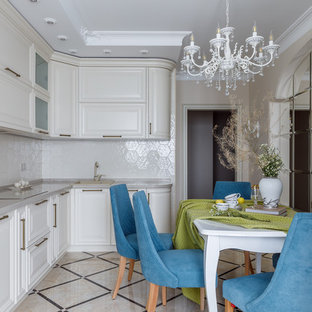 This is an example of a transitional l-shaped eat-in kitchen in Other with a drop-in sink, raised-panel cabinets, beige cabinets, white splashback, white appliances, no island, beige floor and grey benchtop.