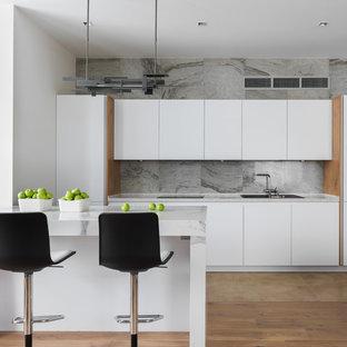 Неиссякаемый источник вдохновения для домашнего уюта: линейная кухня-гостиная в современном стиле с накладной раковиной, плоскими фасадами, белыми фасадами, серым фартуком, коричневым полом и полуостровом
