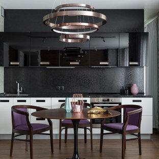 На фото: линейная кухня в современном стиле с обеденным столом, врезной раковиной, плоскими фасадами, черными фасадами, черным фартуком, техникой из нержавеющей стали, коричневым полом и черной столешницей без острова с
